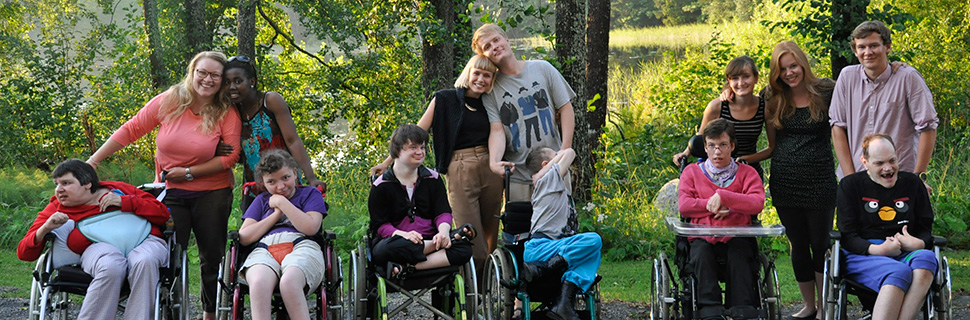 Intellectually disabled people at a summer camp together with staff.