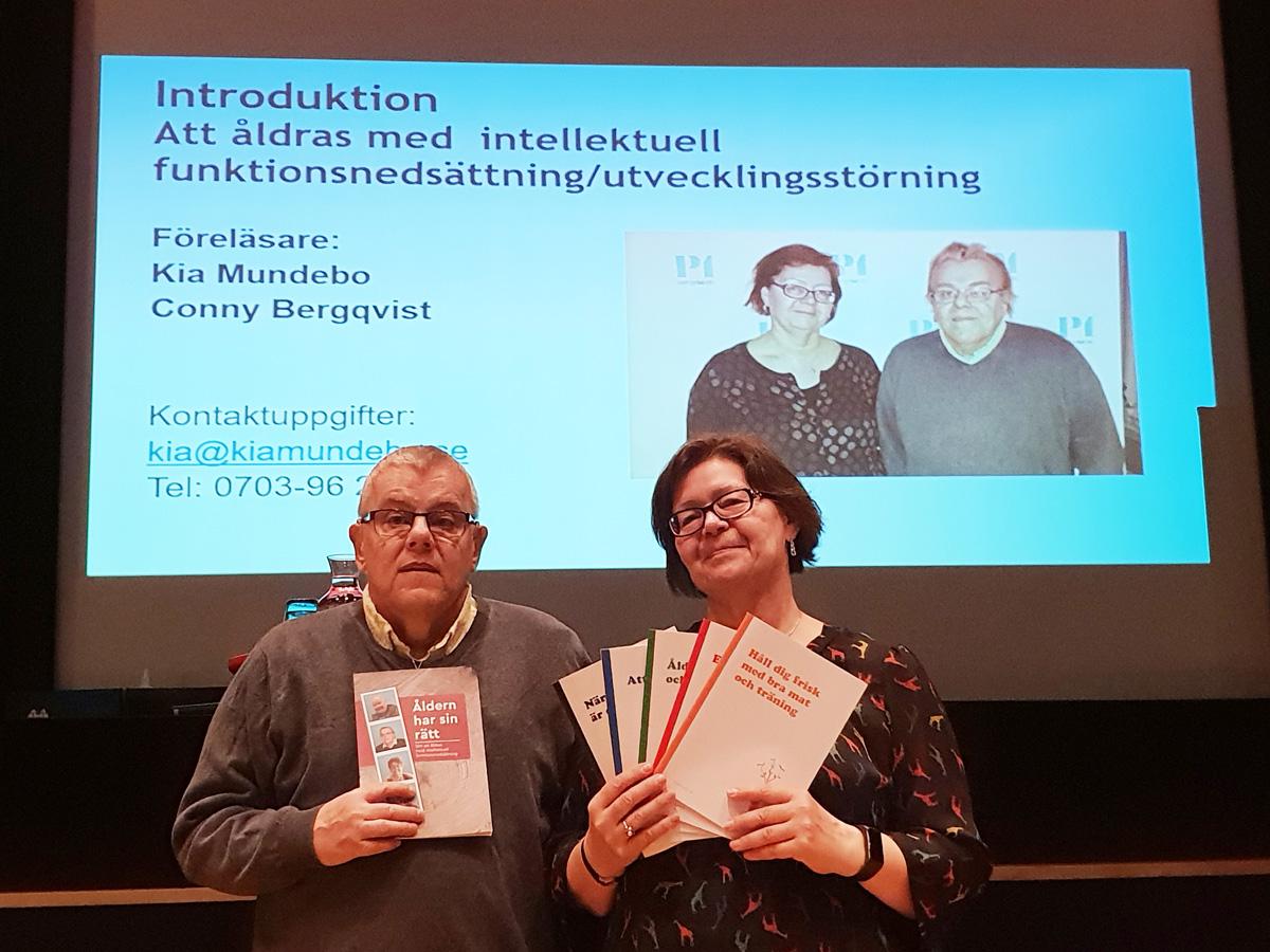 Man och kvinna håller upp broschyrer, i bakgrunden en presentation med texten Introduktion: Att åldras med intellektuell funktionsnedsättning.