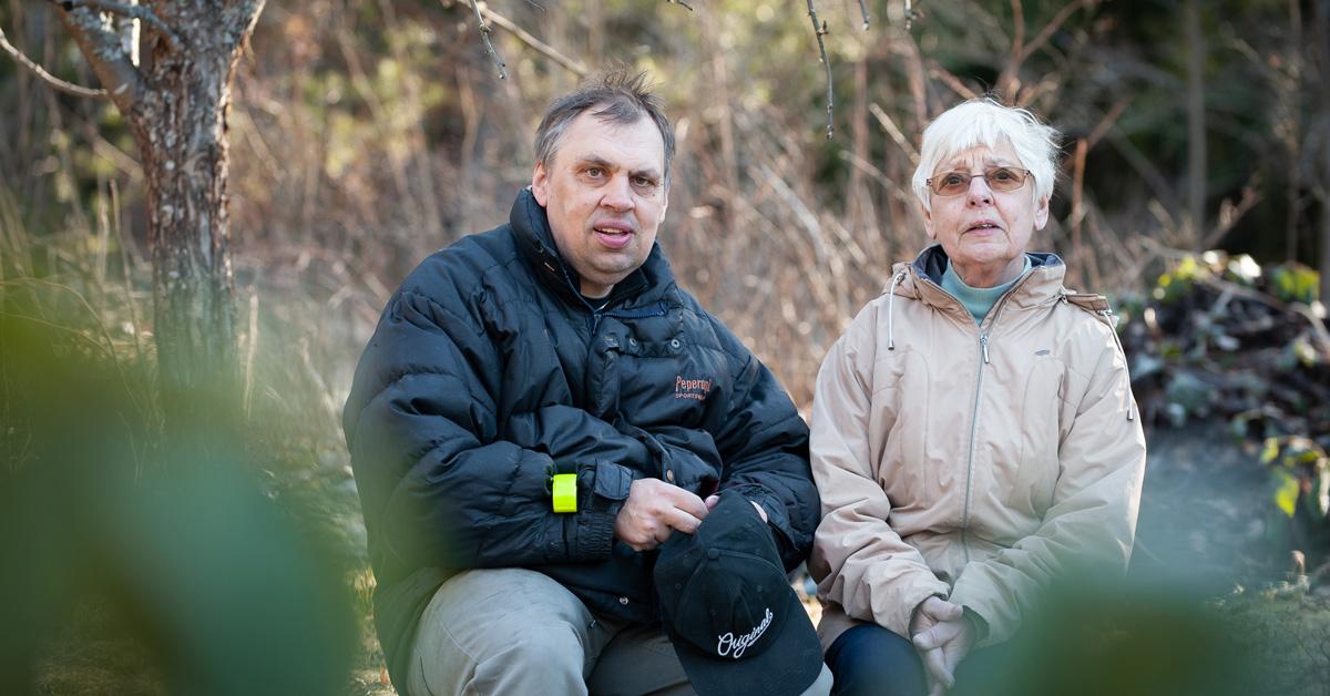 Man och kvinna med grått hår och glasögon i naturen