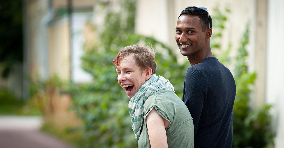 Kvinna med funktionsnedsättning ledsagad av man spatserar glatt på gata.