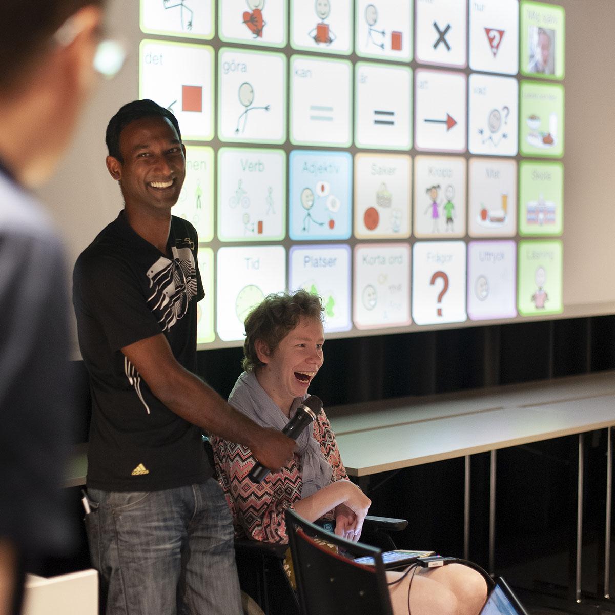 Kinna på stol talar i mikrofon som hålls av assistent. I bakgrunden skärm med flera symbolbilder.