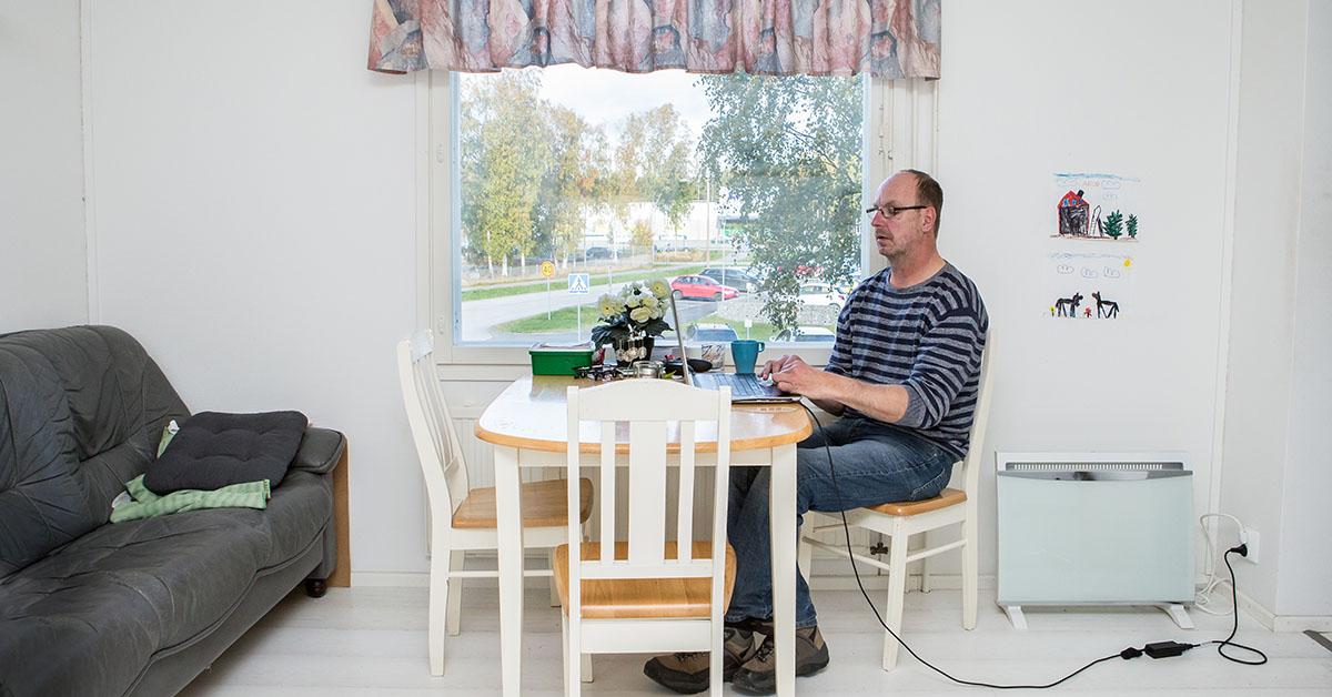 Ensam man i sin lägenhet sitter vid dator.