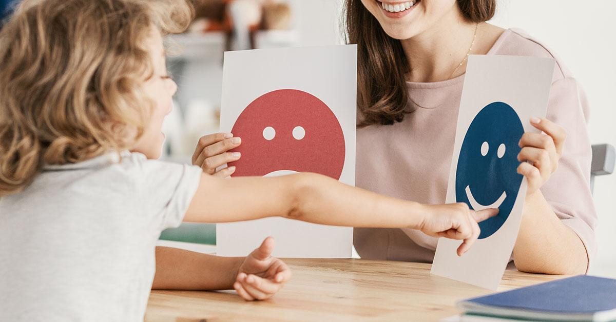 Kivinna håller upp två bilder med glatt och ledset ansikte, barn pekar på den glada.