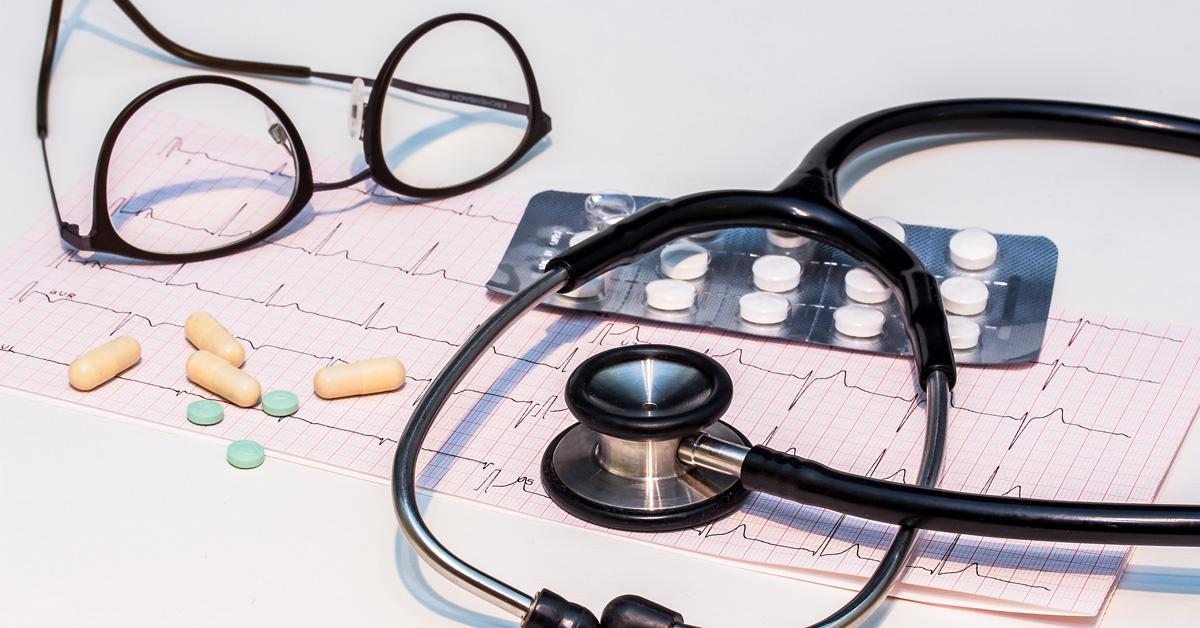 Ett par glasögn, piller, ett stetoskop och en EKG-utskrift