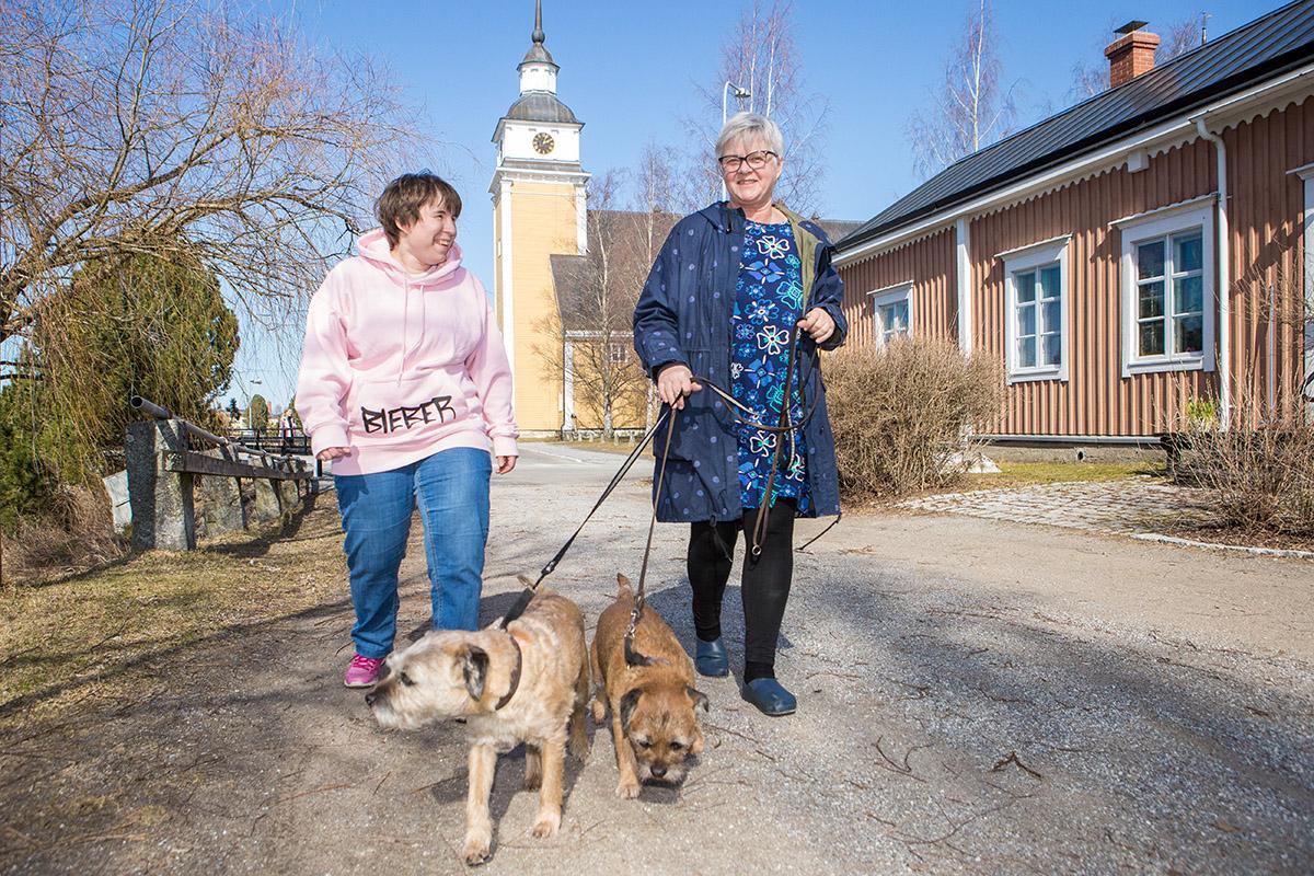 Vuxen dotter och mor på promenad med två hundar.
