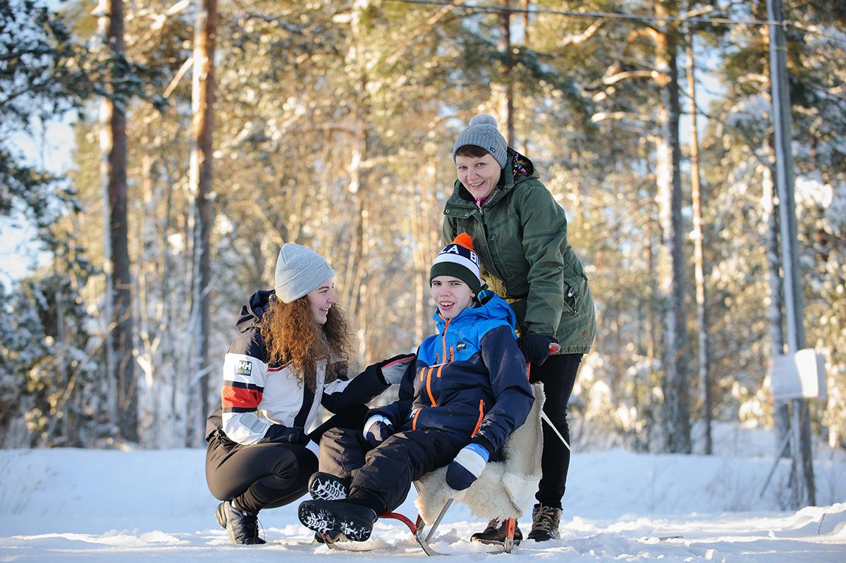 En kille på spartstötting i vinterlandskap, ung kvinna på huk framför honom och bakom står en äldre kvinna.