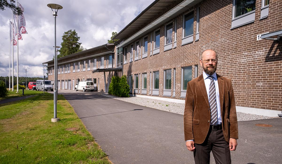 Otto Ilmonen utanför Kårkullas administration och Kårkullas flaggor i bakgrunden.