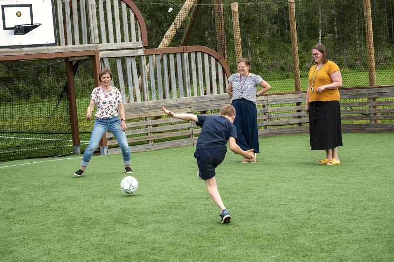 Kille sparkar fotboll mot mål där de tstår en kvinna, två andra kvinnor tittar på och ler.