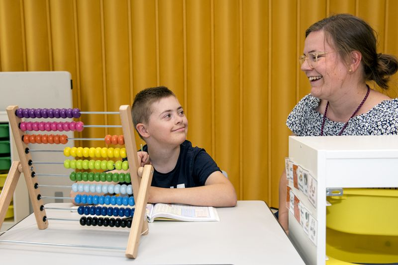 Kille med Downs syndrom sitter med en matematikbok och en kulram tillsammans med vuxen, båda ler.